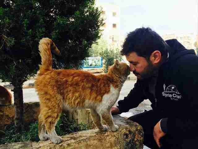 Cat man of Aleppo kisses cat