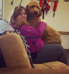 woman hugging dog on couch