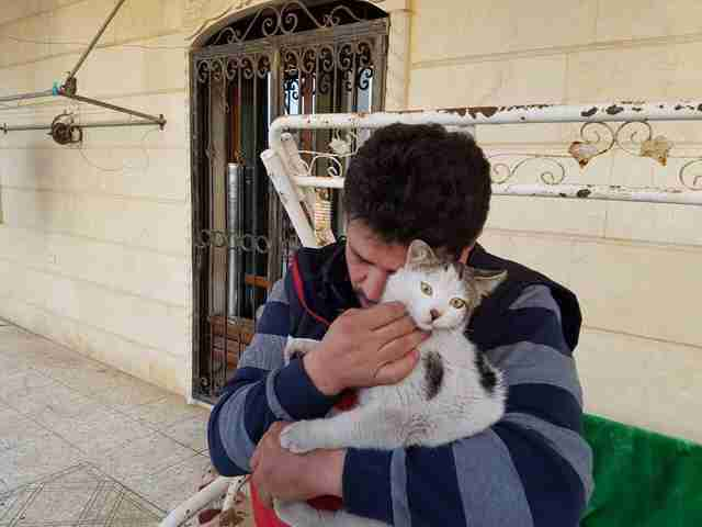Cat man of Aleppo cuddling a survivor of the war