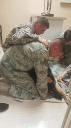 Air force members helping U.S. soldier Kyle Smith put his dog Bodza to sleep
