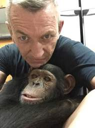 Man holding rescued chimp