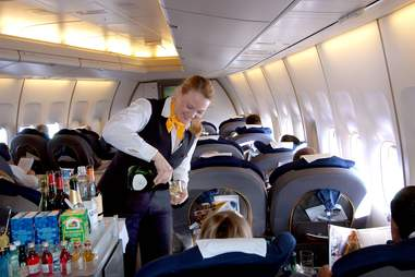 woman on plane pouring booze