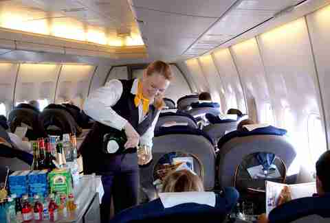 woman on plane pouring booze
