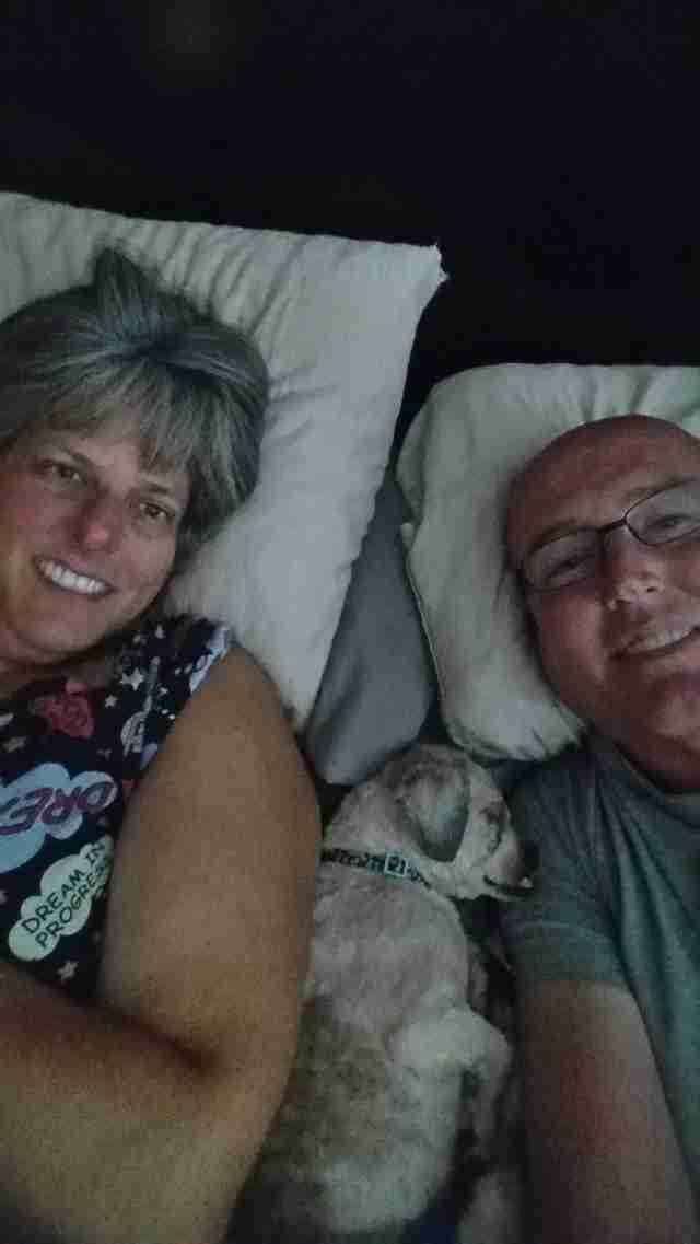 Rescue dog in bed with man and woman