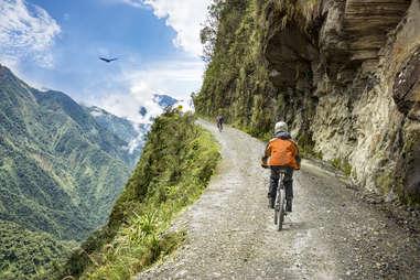 two people biking along a steep mountain road in Bolivia