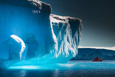 three people in a boat sailing past a giant iceberg