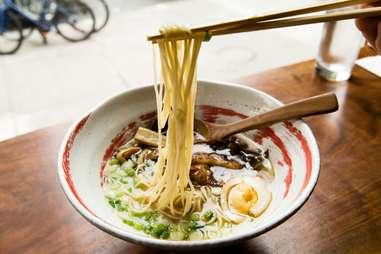 chopsticks plucking noodles out of a bowl of ramen
