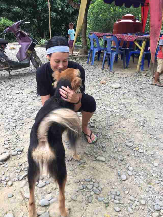 Woman hugging street dog