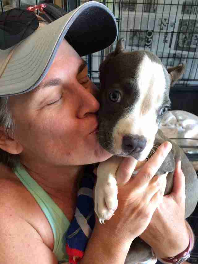 Woman kissing sick puppy
