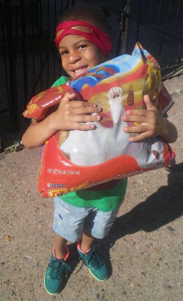 Little boy holding large bag of cat food