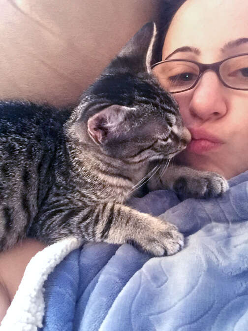 Foster cat snuggles with foster mom