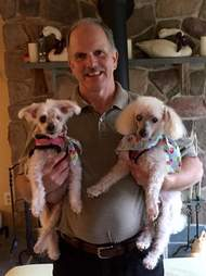 Man holding two senior dogs
