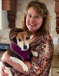 woman holding senior dog in coat