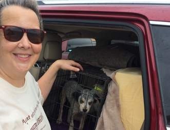 woman with rescue dog in crate
