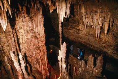people walking through a dark cave