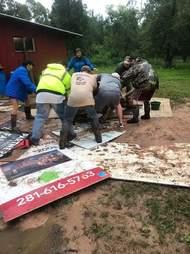 people pulling steer out of mud