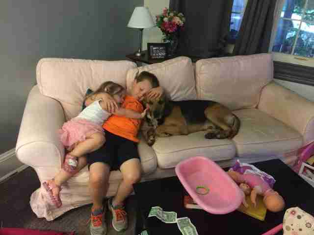 Kids cuddling with rescued hound