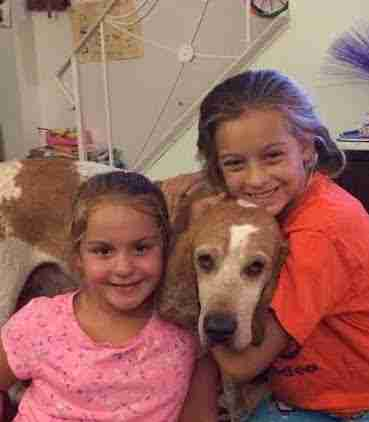 Girls cuddling rescued hound