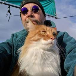 Man with rescue cat on sailboat