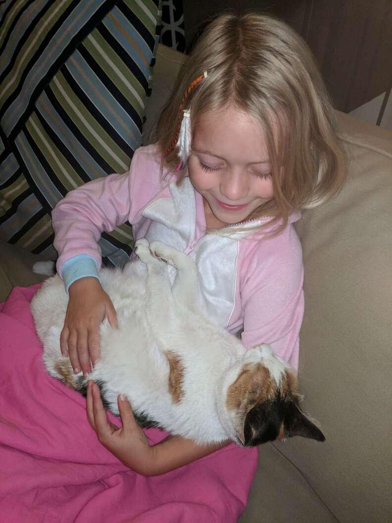 Little girl cuddling cat