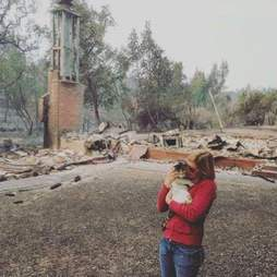 Woman holding cat in front of destroyed house