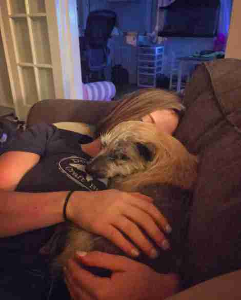 Woman snuggling with rescue dog on couch