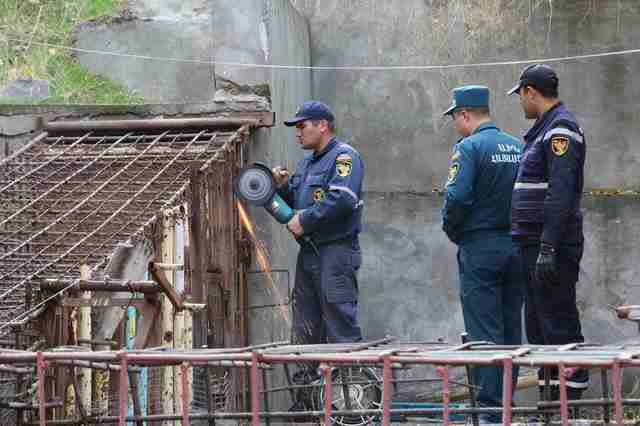 Rescuers sawing through the metal cage of the bears