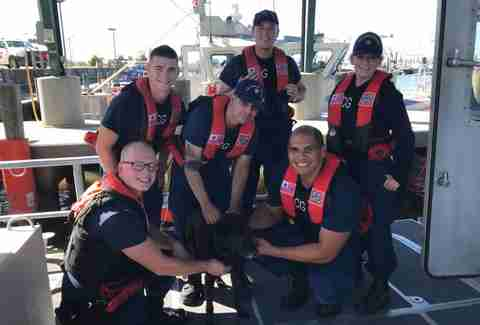 Coast guard rescue team poses with dog