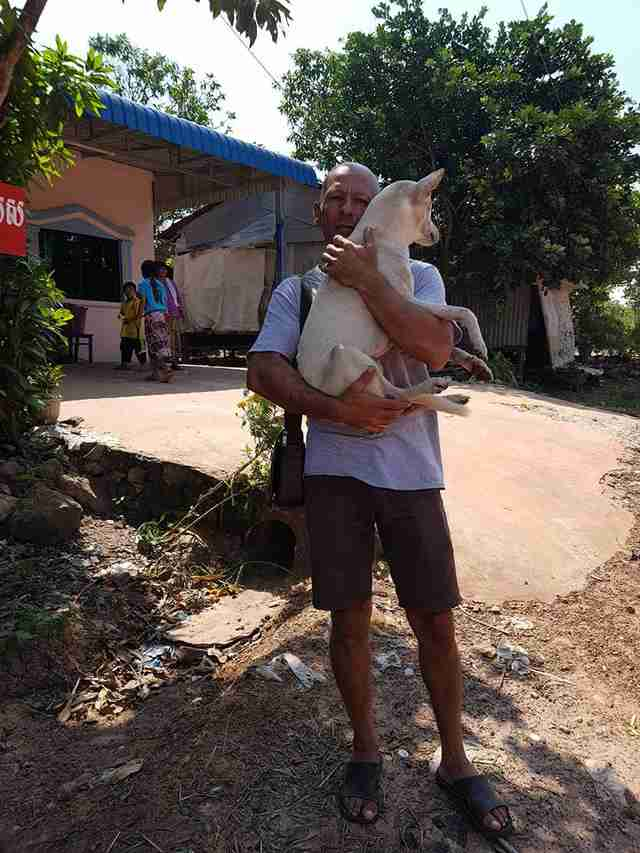 Man holding dog rescued from dog meat restaurant