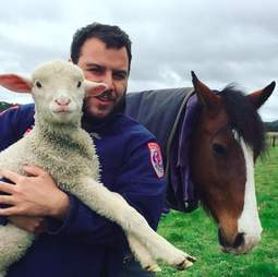 Man holding rescued lamb in his arms