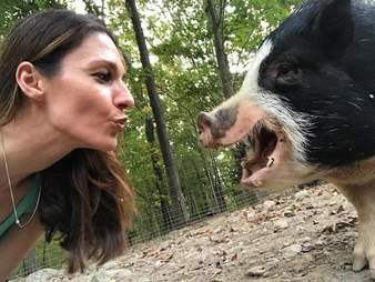 Woman ready to kiss a pig on the snout