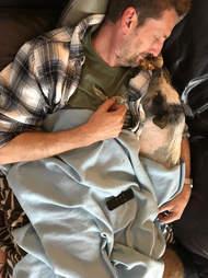 Man cuddling pig in a blanket