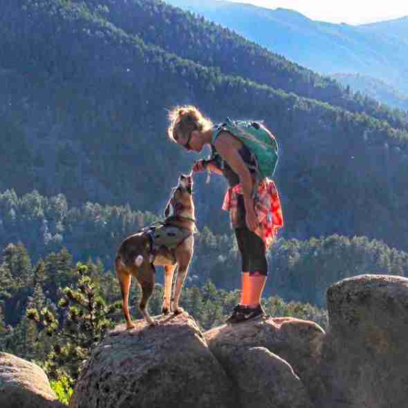 Dog And Woman On Top Of Mountain Peak