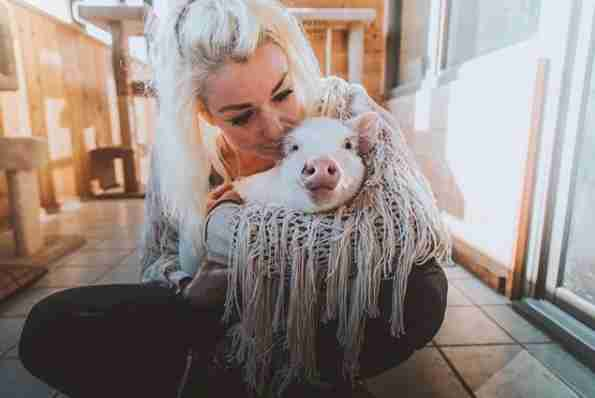 Woman holding rescued piglet