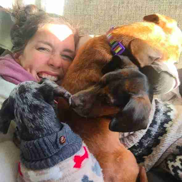Woman cuddling with three dogs