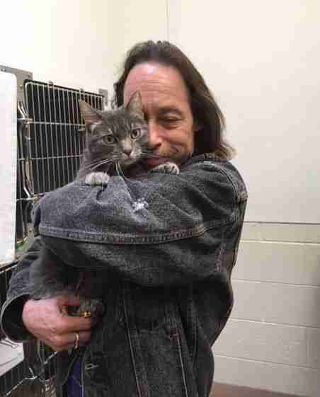 Man hugging his cat at the humane society