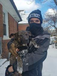 Man holding cold dog in the snow