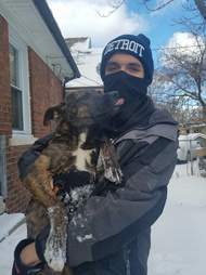 Man holding dog with frostbite