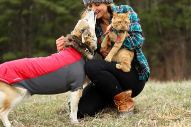 Woman hugging dog and cat outside