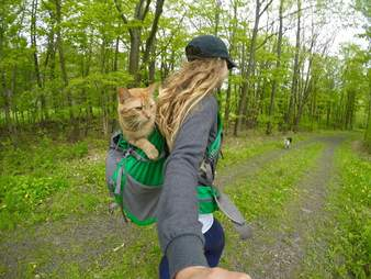 Woman carrying cat inside backpack