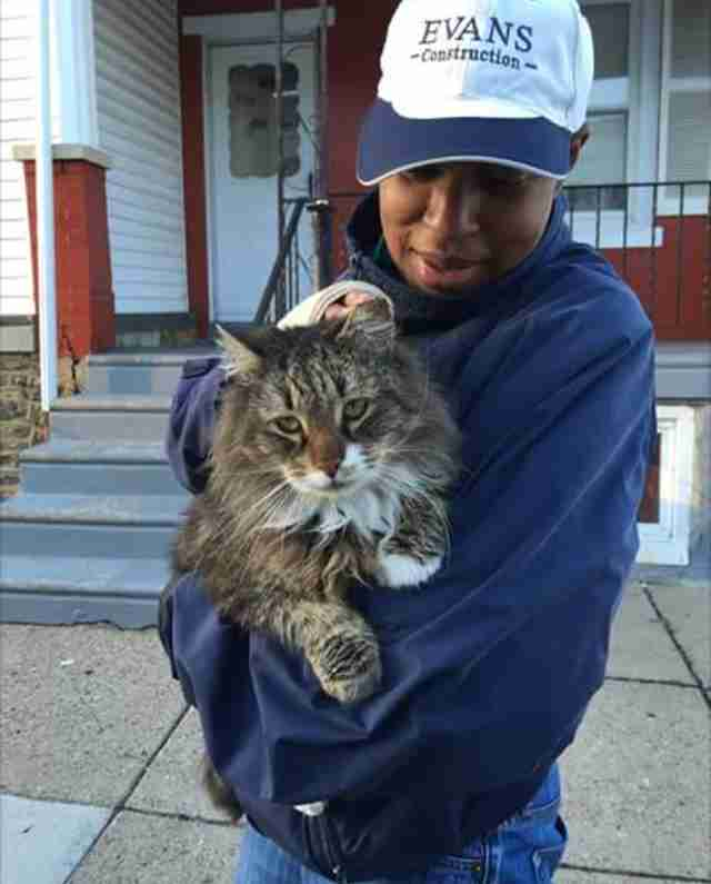 Woman in baseball cap holding a cat in her arms