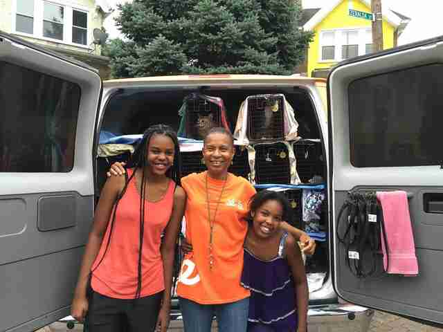 Woman and two girls standing in front of van with cats inside