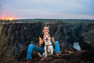 Woman and dog hiking through African bush