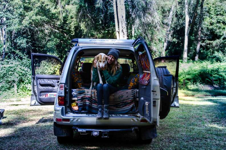 Woman and dog sitting in the back of a vehicle
