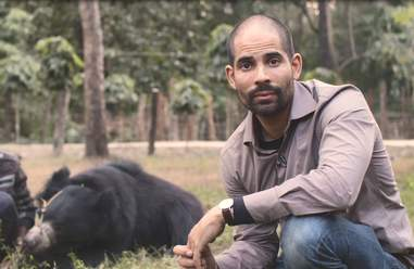 Man posing with bear at forest reserve