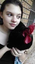 Girl holding rooster against her shoulder