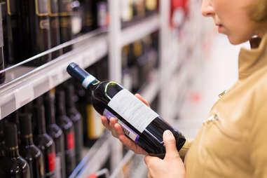 Woman reading back of wine bottle