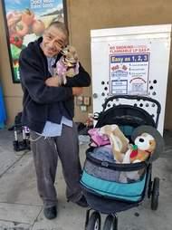 Man hugging dog next to dog stroller