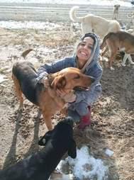 Woman hugging stray dog at garbage dump