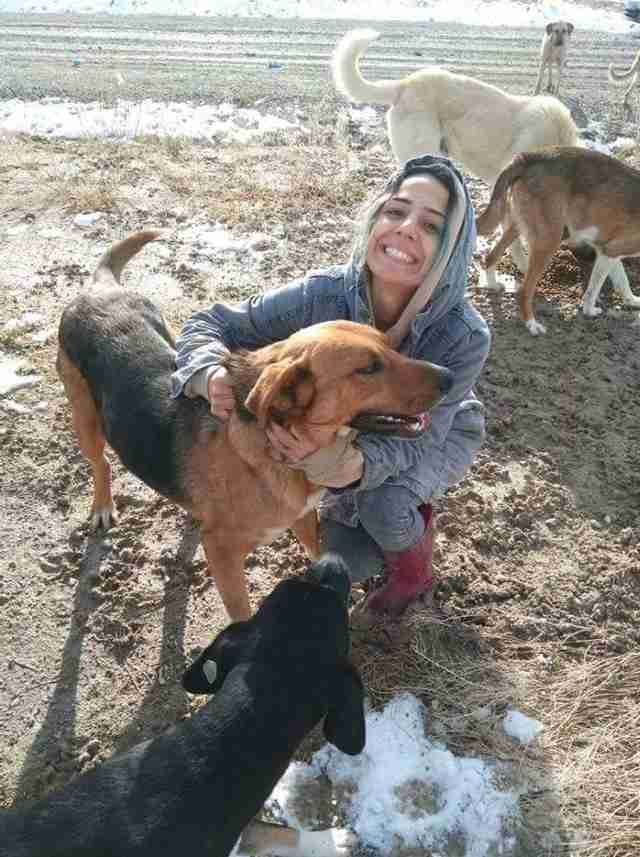 Woman hugging stray dog at garbage dump